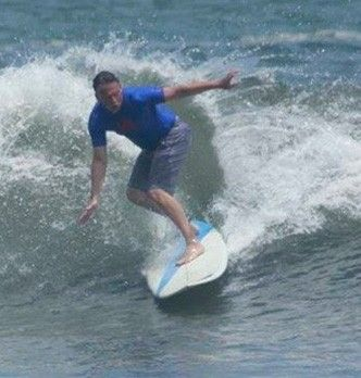 Man in blue shirt surfing in the ocean