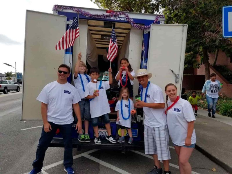 Family posing in front of truck with american flags